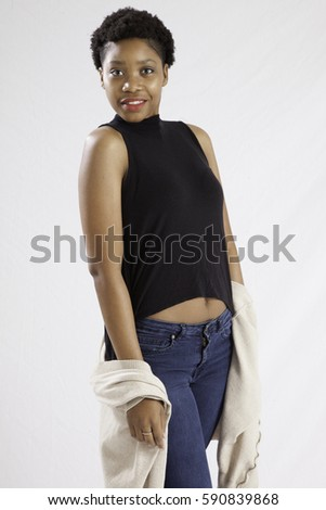 Pretty Black woman in blue jeans, standing and looking happy