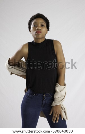 Pretty Black woman in blue jeans, standing and looking pensive