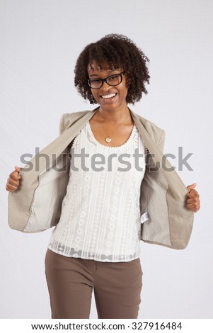 Pretty black woman in glasses   smiling and opening her jacket - stock photo