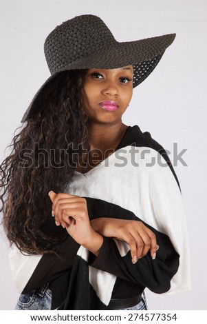 Pretty black woman in hat and black and white blouse, looking at the camera thoughtfully  - stock photo