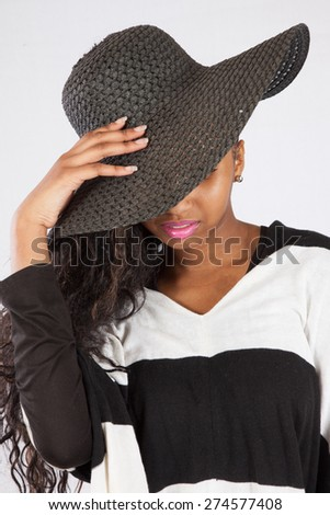 Pretty black woman in hat and black and white blouse, with her hat covering her eyes - stock photo