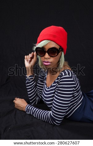 Pretty black woman in stripped blouse and red hat and sunglasses, reclining and looking thoughtful