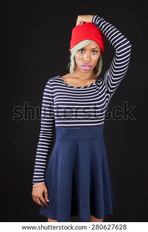 Pretty black woman in stripped blouse and red hat, looking thoughtful with hand on her head - stock photo