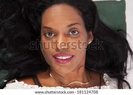 Pretty black woman laying supine and looking at the camera with a friendly expression