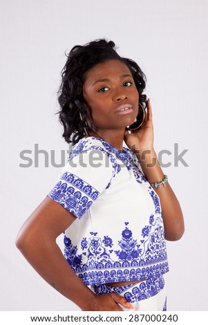 Pretty black woman looking thoughtful with her hand behind her head and the other on her hip - stock photo