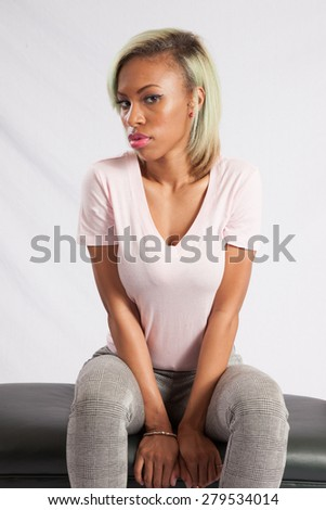 Pretty black woman sitting thoughtfully on a bench