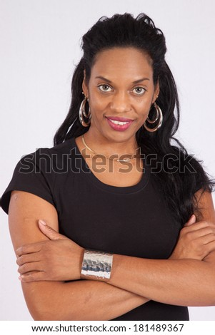 Pretty Black woman standing and looking at the camera  with her arms folded and  a thoughtful, friendly expression
