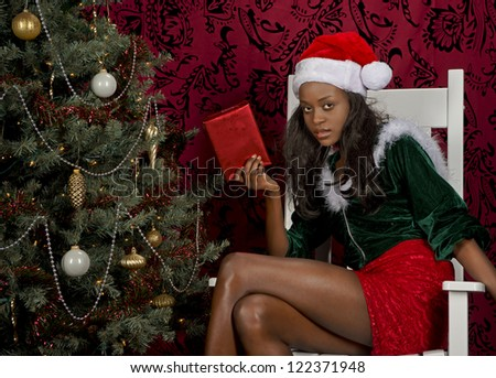 Pretty black woman wearing a green christmas hooded sweater, red skirt and christmas hat holds a present while sitting in a white rocker next to a christmas tree. - stock photo