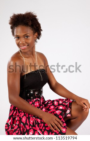 Pretty black woman with eye contact and a happy smile, wearing a black blouse and a colorful red skirt, while she is sitting with her hands on her knees - stock photo