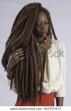 Pretty black woman with long dreadlocks, looking thoughtful