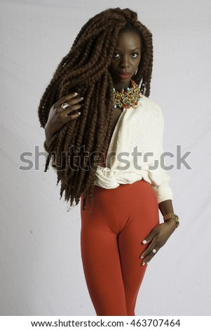 Pretty black woman with long dreadlocks, looking thoughtfully at the camera