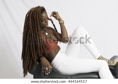 Pretty Black woman with long dreadlocks, sitting on a bench and looking thoughtful
