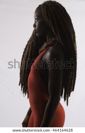 Pretty Black woman with long dreadlocks, standing in profile and looking thoughtful