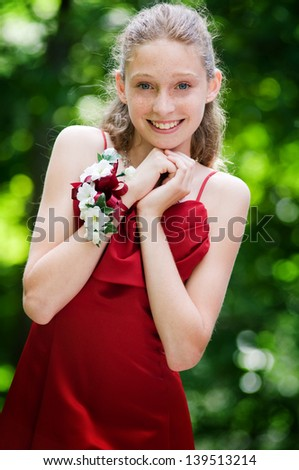 pretty blond blue eyed teen girl dressed in a gown to attend the school prom - stock photo
