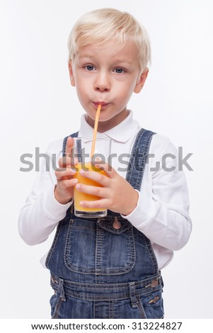 Pretty blond boy is drinking orange juice through a straw with enjoyment. He is standing and holding a glass. The boy is looking at the camera happily. Isolated
