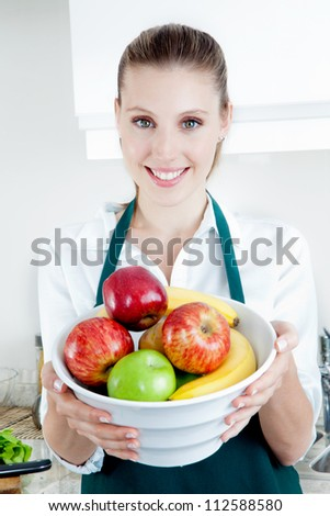 Pretty blond female holding bowl with a smile in kitchen