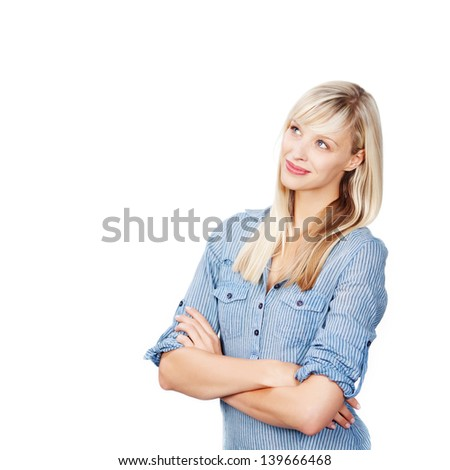Pretty blond female looking up and thinking with crossed arms