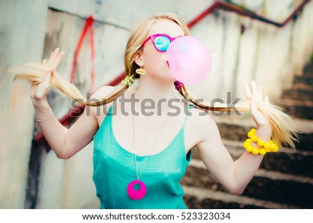 Pretty blond girl chewing gum and making bubbles