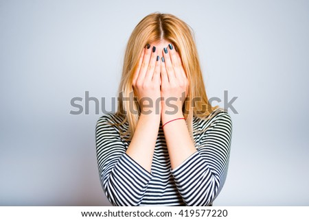Pretty blond girl frightened and hides her face in her hands - stock photo
