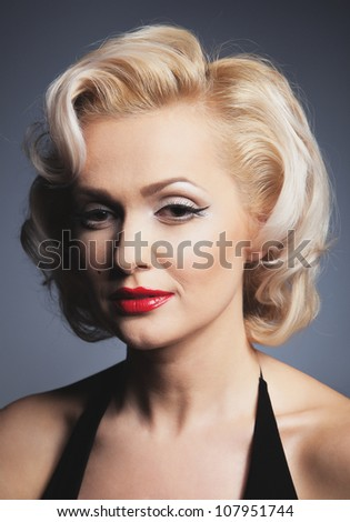 Pretty blond girl model like Marilyn Monroe in red dress with red lips on gray background - stock photo