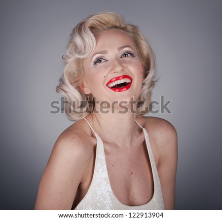 Pretty blond girl model like Marilyn Monroe in white dress with red lips on gray background - stock photo