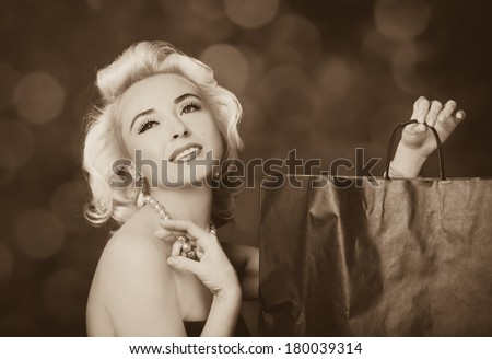 Pretty blond girl model like Marilyn Monroe with shopping bag on red background - stock photo