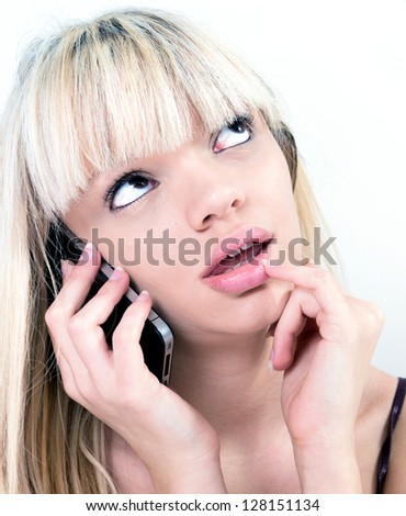 pretty blond girl pondering while phoning - stock photo