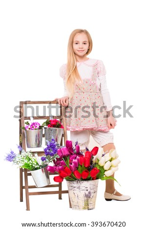 Pretty blond girl posing near flowers. Isolated on white - stock photo