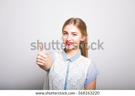 Pretty blond girl showing thumbs up gesture, cool, isolated - stock photo