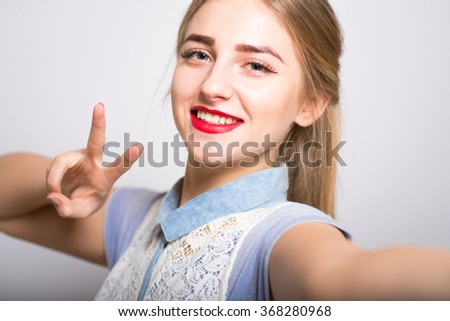Pretty blond girl showing two finger gesture, isolated - stock photo