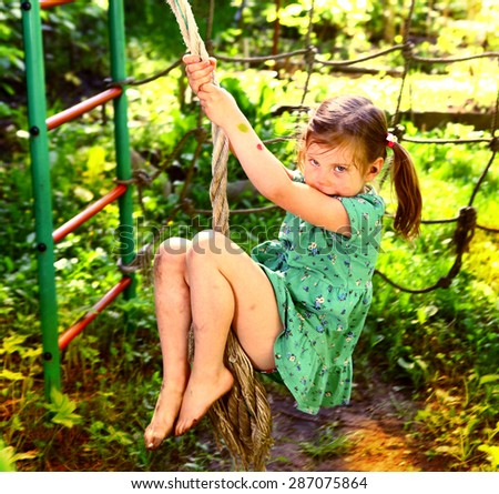 pretty blond girl swinging on the outdoor summer play ground - stock photo