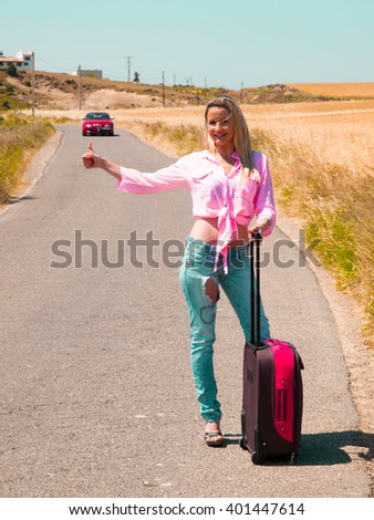 pretty blond girl walking on the road with her suitcase