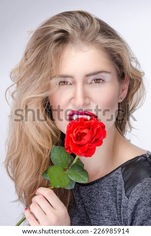 Pretty blond girl with vampire fangs and bright makeup biting a flower. Halloween witch - stock photo