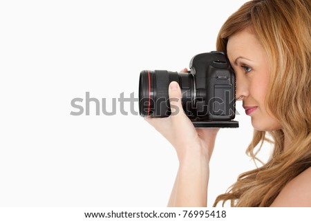 Pretty blond-haired woman taking a photo with a camera on a white background