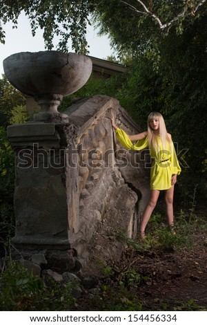 Pretty blond in a yellow dress stands near old castle surrounded by the trees and grass