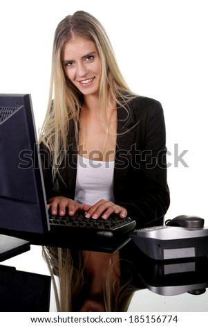 Pretty blond office secretary lady smiling while she types on keyboard on her desk - stock photo