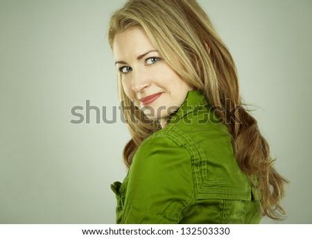 pretty blond wearing green dress on light background - stock photo
