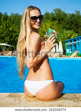Pretty blond woman enjoying cocktail in a swimming pool - stock photo