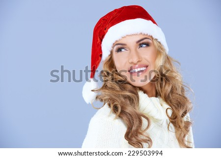 Pretty blond woman in a red Santa Hat with a merry smile looking over her shoulder to blank copyspace on blue for your Christmas greeting - stock photo