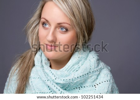 Pretty blond woman in a winter sweater over gray background - stock photo