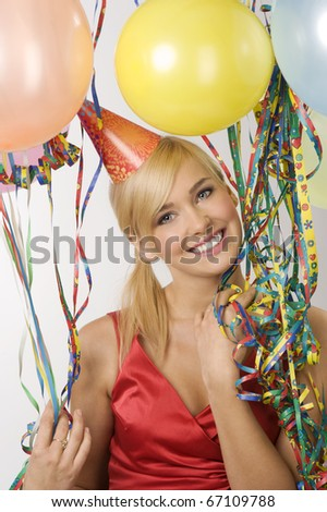 Pretty blond woman in red dress with a funny hat balloons and colored ribbons during a party - stock photo