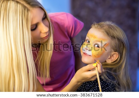 Pretty blond woman painting the face of a little girl - stock photo