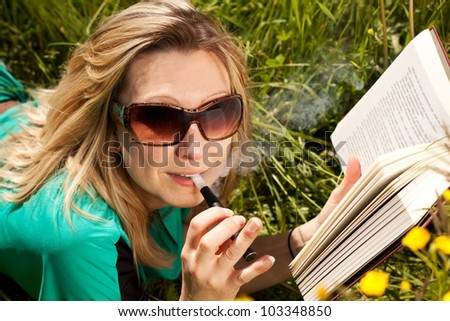 pretty blond woman reading , and evaporated to an electric cigarette - stock photo