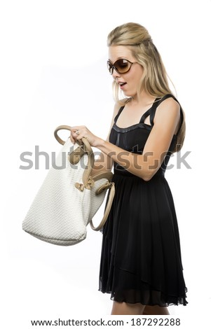 Pretty blond woman searching through her purse - stock photo