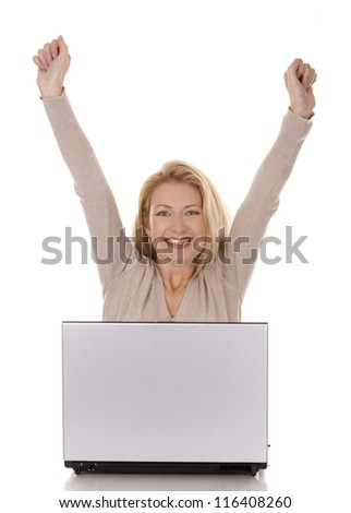 pretty blond woman wearing beige swether, sitting down and using laptop - stock photo