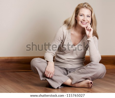 pretty blond woman wearing beige top relaxing on the floor