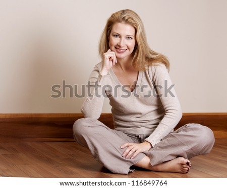 pretty blond woman wearing beige top relaxing on the floor - stock photo