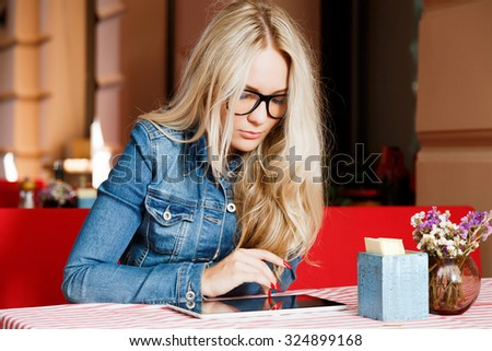 Pretty blond woman, wearing in glasses, white shirt and blue jacket, sitting at the table with tablet, in cozy cafe, on summer day, waist up - stock photo