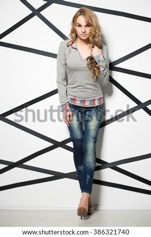 Pretty blond woman wearing jeans and grey blouse posing in the studio - stock photo