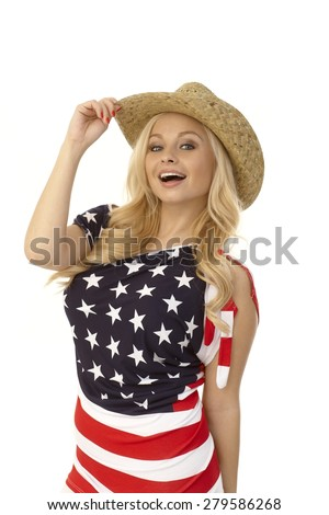 Pretty blonde American woman posing in American flag t-shirt and straw hat, smiling. - stock photo